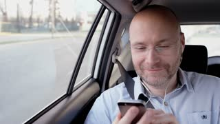 Bald Businessman Looking at a Mobile and Smiling