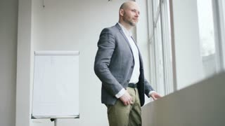 Bald Businessman Moving Closer to a Window