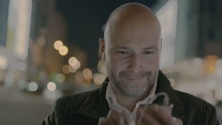 Bald Businessman Smiling While Using a Mobile Phone