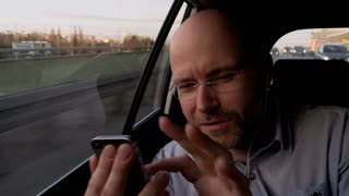 Bald Businessman Using a Mobile and Then Looking at It