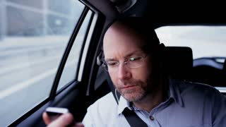 Bald Man in the Car Connecting Heaphones to his Phone