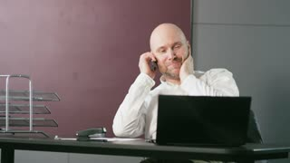 Bald Middle-Aged Businessman Ending a Nice Phone Call