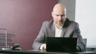 Bald Middle-Aged Businessman Having a Headache