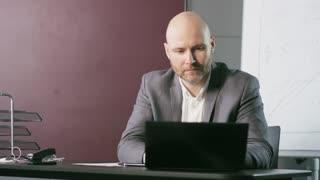 Bald Middle-Aged Businessman Receives Strange News