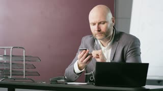 Bald Middle-Aged Businessman Using a Mobile Phone