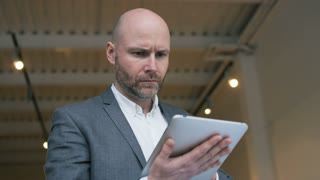 Bald Middle-Aged Businessman Using a Tablet Computer