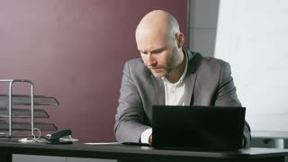 Businessman Looking Nervously at a Laptop Computer