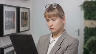 Businesswoman Holding a Tablet and Putting on Glasses