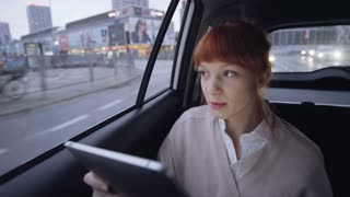 Businesswoman in the Car Using a Tablet and Smiling