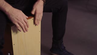 Hands and Face of a Bald Man Playing Cajon