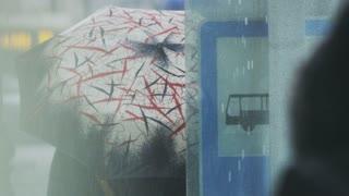Hooded Woman Walking Near the Bus Stop in the Rain