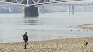 Little Girl is Playing on the River Beach. Woman Looks at Her