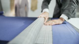 Man in a Suit Unrolling a Grey Checked Piece of Material