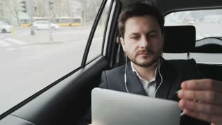 Man in the Car Connecting Headphones to a Tablet