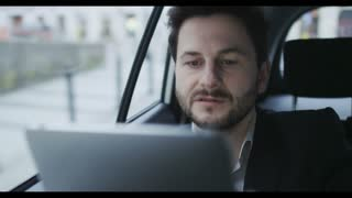 Man in the Car Focused on Work With a Tablet Computer