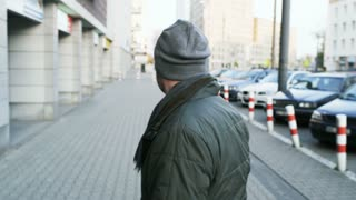 Man Turning to the Camera and Walking Down the Street