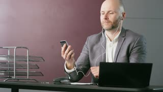 Man Wearing Headphones and Starting a Phone Call