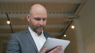 Middle-Aged Businessman Focused on Work with Tablet