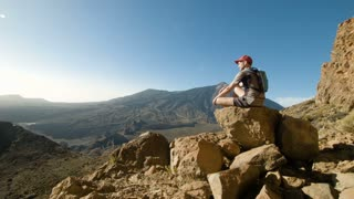 Mountain Hiking. Tired Young Man Sitting Still on a Rock