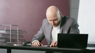Nervous Bald Businessman Playing With a Ballpen