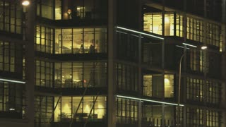 People Working in Tall Office Building. Street Lamp