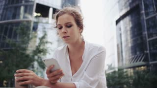 Sad Young Businesswoman Looking at Her Mobile Phone