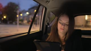 Sleepy Young Businesswoman Using a Tablet in the Car