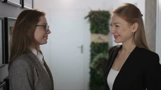 Two Young Businesswomen Giving a High Five and Smiling