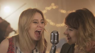 Two Young Female Vocalists Singing to the Microphone
