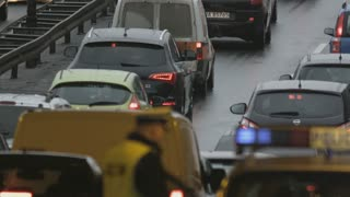 Vehicles Stuck in a Traffic Jam. Policeman Getting Into a Car