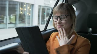 Woman Looking at the Tablet With one Hand on her Chin