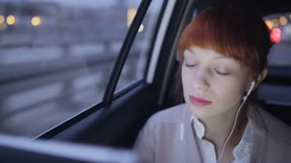 Woman Sitting in the Car and Taking Headphone Off