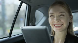 Woman Smiling While Using a Tablet in the Moving Car