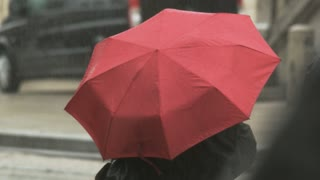Woman With a Big Red Umbrella Waiting at the Bus Stop