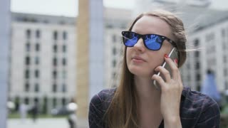Woman With Dark Glasses Laughing During a Phone Call