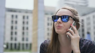 Woman With Dark Glasses Looking Up During a Phone Call