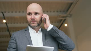 Worried Bald Businessman Talking on the Phone