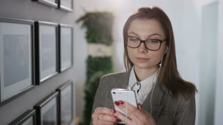 Young Businesswoman in Glasses Putting a Headphone On