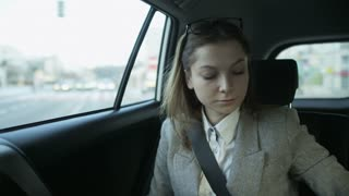 Young Businesswoman Using a Mobile in the Moving Car