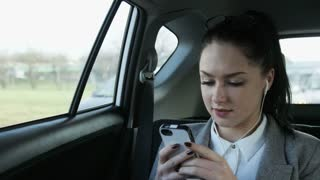 Young Businesswoman Using a Mobile Phone in the Car