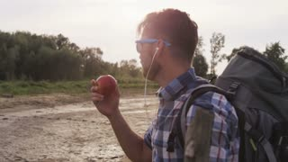 Young Man Eating an Apple in the Wild