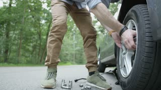 Young Man Removing a Tire and Walking to the Trunk
