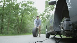 Young Man Rolling a Spare Tire From the Front of his Car