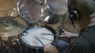Young Man Wearing Headphones and Using Drum Brushes