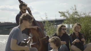 Young People Playing Musical Instruments at the River