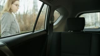 Young Woman Getting Into the Car and Fastening a Seat Belt