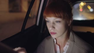 Young Woman in the Car Using a Tablet and Raising Eyes