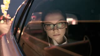 Young Woman Putting a Headphone On. The Car Stops
