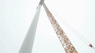Wind Turbine Tower and a Crane. Camera Moving Down