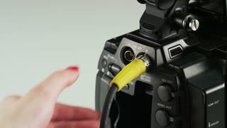 Woman Re-plugging a Yellow Cable to a Video Camera